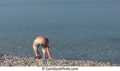 boy stands on pebble beach and throws stones