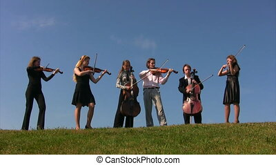 six musicians plays stringed instruments on hill against sky
