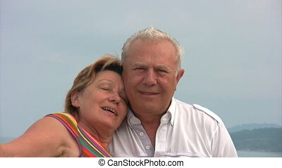 senior couple stands against sky and sea