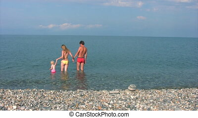 family with little girl has fun in sea