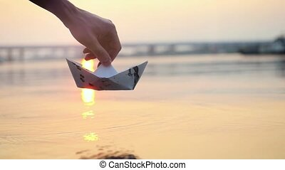 Man's hand putting paper boat on the water and pushing it...