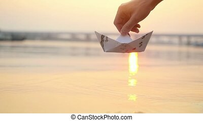 Man's hand launches paper boat on the water and pushing it...