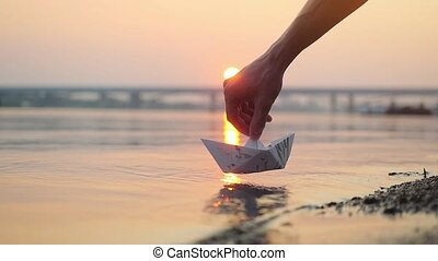 Man's hand putting paper boat on the water and pushing it away during beautiful sunset with reflection sun in the sea in slowmotion, as in childhood.