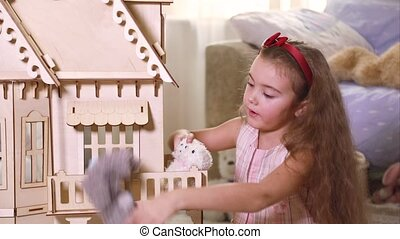 Girl playing with a doll-house - Seven years old girl...