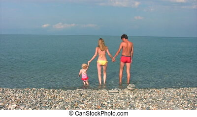 family walks on rocky coast, quiet sea in background