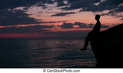 silhouette of youngster sitting against sunset sky and...