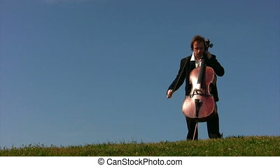 musician in classical suit plays violoncello on field...