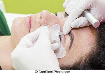 Woman on the procedure for eyelash extensions, eyelashes lamination