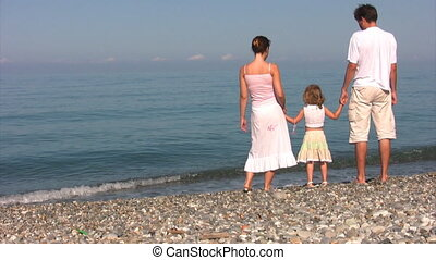 family stands on coast against sea