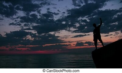 youngster stands on rock against sunset sky and sea