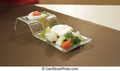 Breakfast, poached egg with boiled vegetables on the table