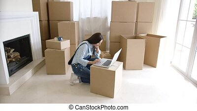 Young woman using a laptop on a cardboard box as she catches...