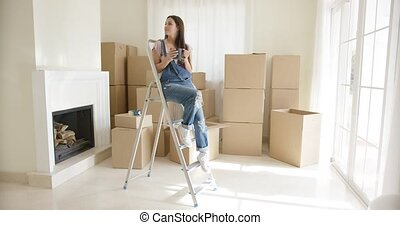 Young woman sitting on a stepladder in a room full of boxes...