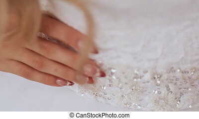 A brilliant wedding dress and beautiful manicure on hands of...