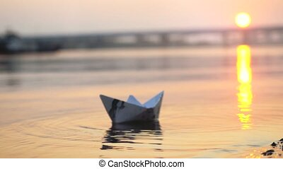 Man's hand putting paper boat on the water and pushing it away during beautiful sunset with reflection sun in the sea.
