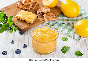 lemon curd in glass cup. blueberry and mint on white wooden...