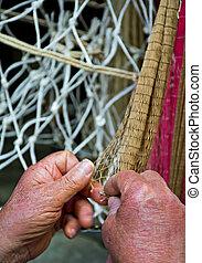 Artigiano che lavora e intreccia i fili