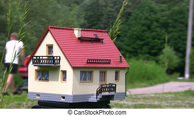 toy house standing outdoor, defocused people in background -...