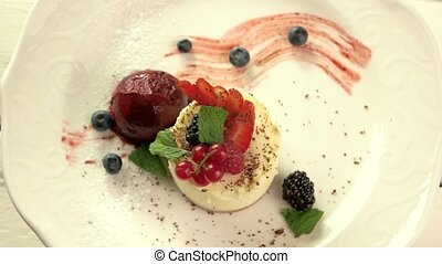 Mint leaves on small cake. Ice cream ball and berries....