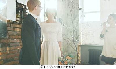 Bride and groom at wedding ceremony kiss after registrar...
