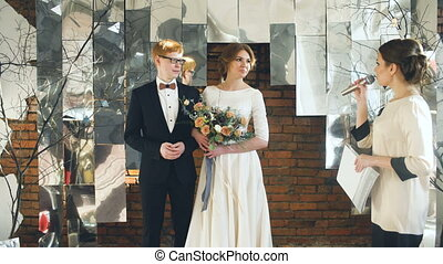 Bride and groom at wedding ceremony listen to registrar...