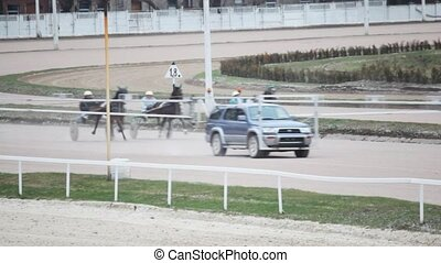 off-road car on hippodrome goes ahead of teams with horses and jockeys to them