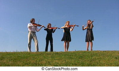 four musicians plays violins on hill