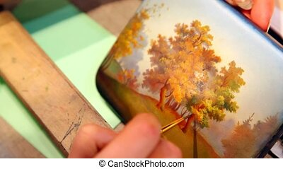 hand holds brush and draws miniature in form of autumn trees...