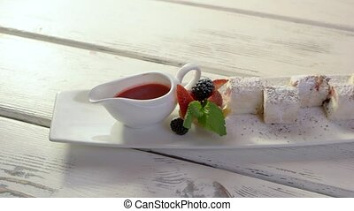 Dessert with berries on plate. Fruit tartlet and sauce jug....