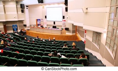 presentation hall with rows of seats, listeners in them and...