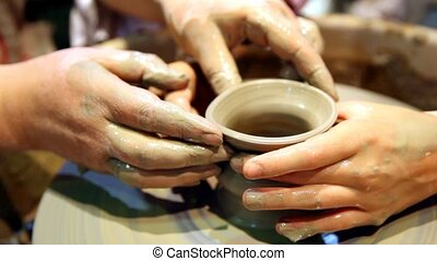 hands form pot rotating on potters wheel - two pairs hands...