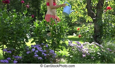 Hot garden worker woman in shorts and bra watering flowers in summer time garden. 4K