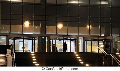 workers of offices leave revolving doors of building -...