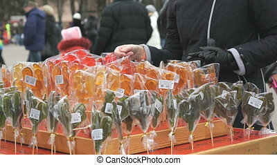 Customer choosing sweet sugar lollipops at store - Customer...