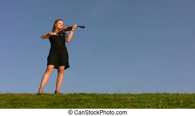 young woman stands on hill and plays violin - young woman...