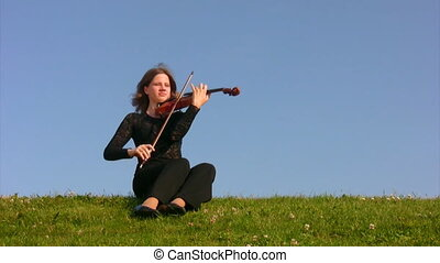 woman sits on meadow and plays violin - young woman sits on...