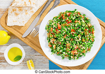 parsley, mint, tomato salad orTabbouleh on white platte -...