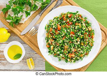 parsley, mint, tomato salad orTabbouleh on white platter on...