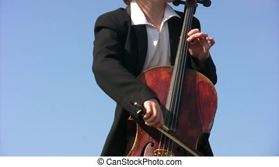 unidentified man plays violoncello, sky in background