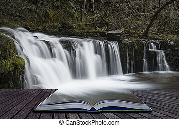 Beautiful waterfall landscape image in forest during Autumn Fall in Wales UK coming out of pages of book