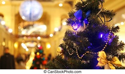 New Year's tree with blinking garlands in shopping centre -...