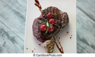 Steak on plate spinning. Grilled meat with cherry tomatoes....