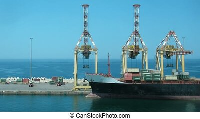 Loading of cargoes on the cargo ship on sunny day, forward...
