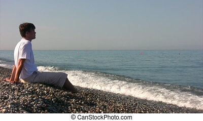 bespectacled man sitting on beach throws pebbles into sea -...