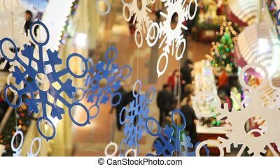 paper snowflakes on cords, against shopping centre pavilions