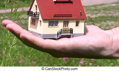miniature model of house on palm brings to camera and takes...
