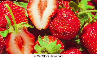 macro of strawberries with two halfs in the center spinning in circles close up