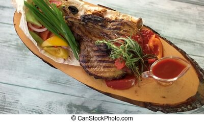 Top view of grilled pork. Sauce jug on wooden board. Enjoy...