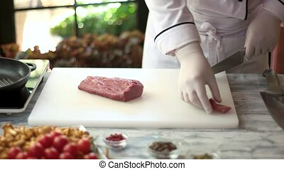 Chef cutting raw meat. Pieces of veal. Cooking master class.