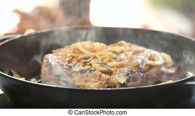 Cooking steak in pan. Meat and pieces of onion. How to...